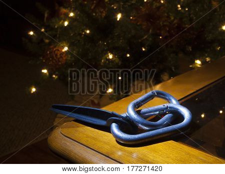 Carabiners and a piton on a table with Christmas tree behind