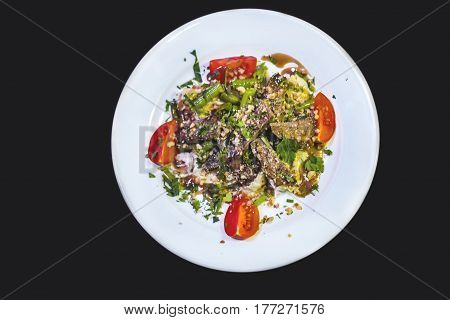 Meat with vegetables on a white plate isolated on a black background