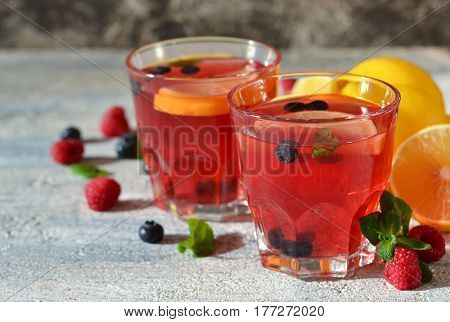 Cold berry drink with lemon and mint on a concrete background