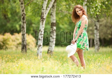 Young redhead woman walking in the park with flowers. Beauty nature scene with colorful background. Outdoor lifestyle. Happy woman relax in summer park