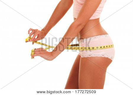 Woman body with measure tape. Close up of sporty and beautiful female body. Tanned woman measuring waist and hips with measuring tape. Healthy lifestyle, dieting, fitness, weight loss concept