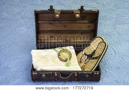 Open vintage suitcase packed with towel tropical bracelet necklace and flip flop sandals travel concept