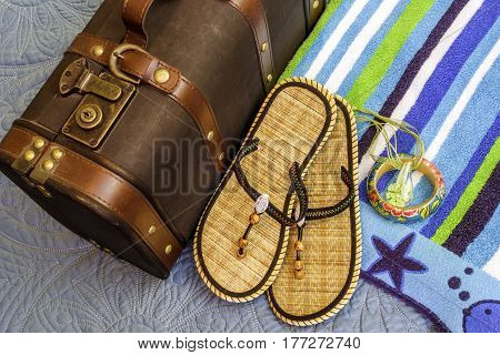 Closeup of beach towel sandals and other items ready to be packed in a vintage suitcase for tropical travel