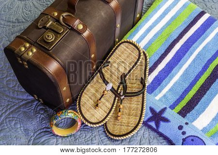 Beach towel sandals and tropical bangle bracelet beside old vintage suitcase travel concept