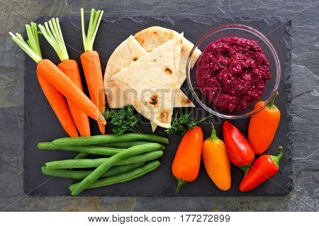 Beet Hummus Dip With A Platter Of Fresh Vegetables, Above View On A Slate Background