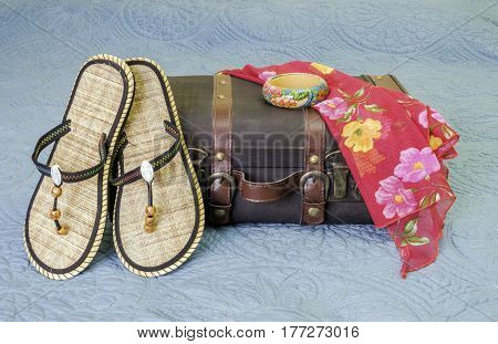 Tropical sandals scarf and bracelet sitting on a vintage leather suitcase travel concept
