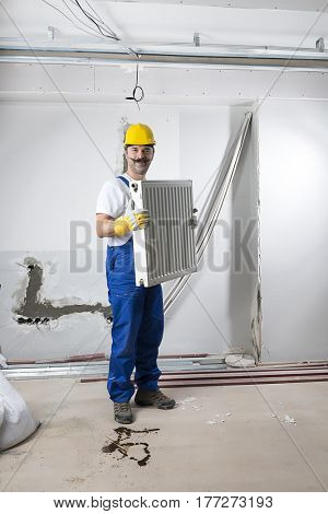 Construction worker with mustache carrying heating radiator.