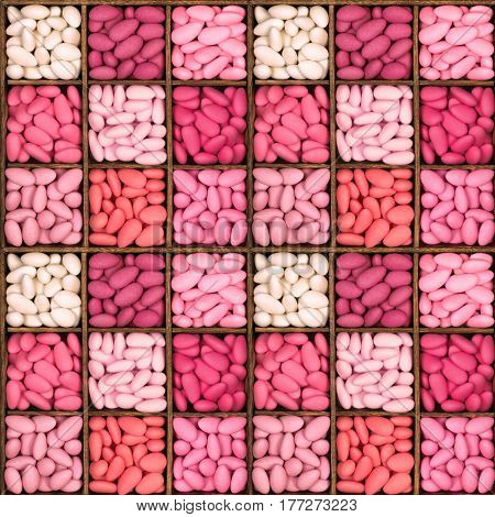 A seamless pattern of a square wooden storage box with nine compartments, filled with a selection of sugared almonds in shades of pink. These bitter sweet treats are a traditional wedding favour.