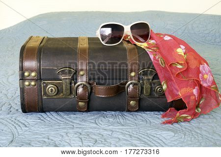 Leather vintage suitcase with tropical scarf and sunglasses draped on top travel concept