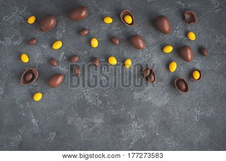 Easter concept. Chocolate easter eggs on dark background. Flat lay top view