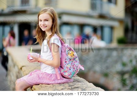Adorable Little Girl Eating Tasty Fresh Ice Cream Outdoors On Warm Summer Day