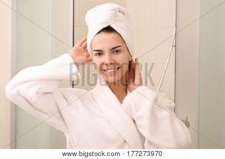 Beautiful young woman wearing bathrobe in shower