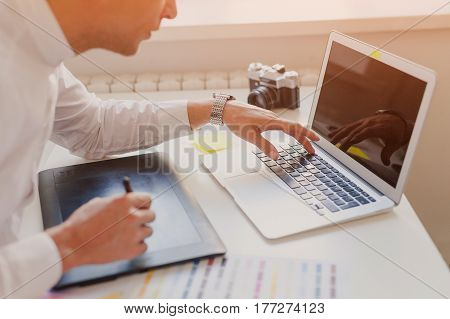 The designer using the laptop during work with graphic tablet. Horizontal indoors shot