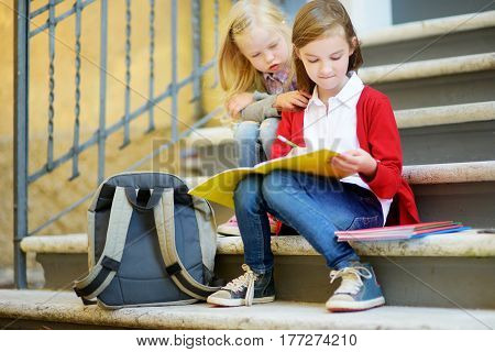 Adorable Little Schoolgirls Studying Outdoors On Bright Autumn Day. Young Students Doing Their Homew