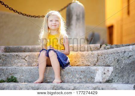 Adorable little girl sitting on the stairs on warm and sunny summer day in Gargnano town in Italy