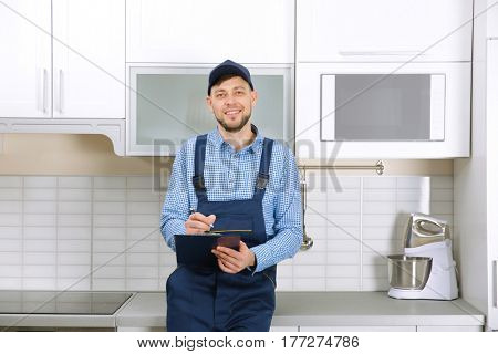 Plumber in uniform holding clipboard at kitchen