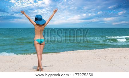 Happy woman on the beach by the sea