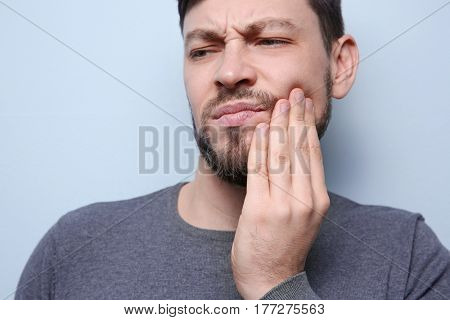 Handsome man suffering from toothache on color background