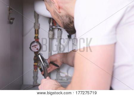 Plumber repairing sink pipes in kitchen, closeup