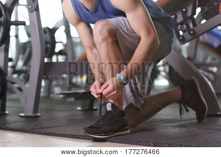 Young man with fitness tracker tying shoelaces in gym