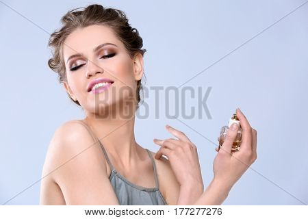 Beautiful young woman with bottle of perfume on color background