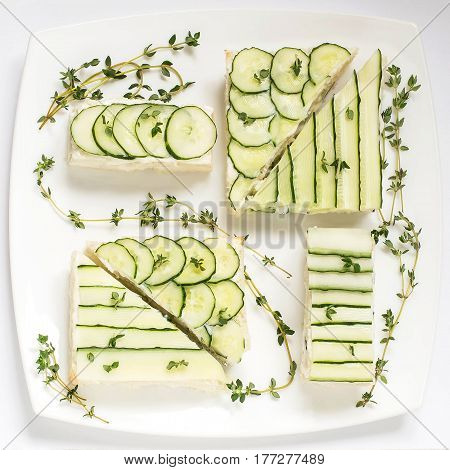 Delicious spring sandwiches with cream cheese fresh cucumbers and thyme leaves on a plate on a white background. Square image