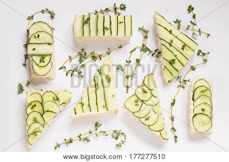 Delicious spring sandwiches with cream cheese fresh cucumbers and thyme leaves on a white background