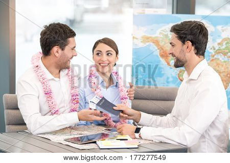 Young man and couple sitting in office travel agency