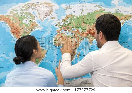 Young man and woman standing near map in travel agency office