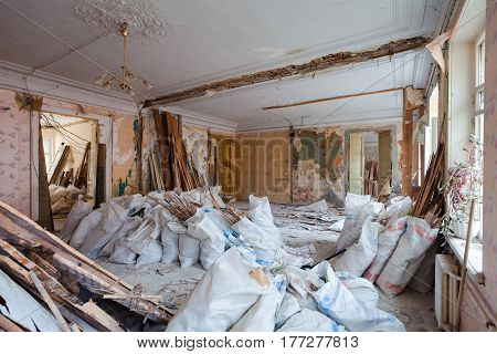 View of the vintage room with fretwork on the ceiling of the apartment and retro chandelier during under renovation remodeling and construction. The process of disassembly old room and packing constraction garbage into the sacs.