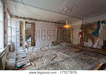 View the vintage room with fretwork on the ceiling of the apartment during under renovation remodeling and construction. Ladder garbage of constraction materials and lamp in dark room during of disassembling floors and walls.