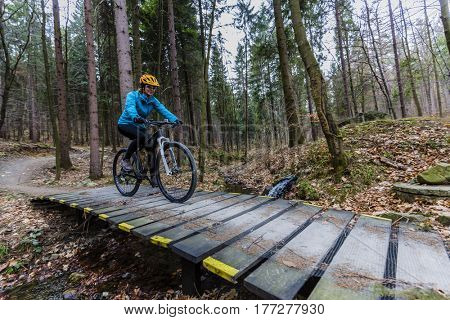 Mountain biking women riding on bike in early spring mountains forest landscape. Woman cycling MTB enduro flow trail track. Outdoor sport activity.