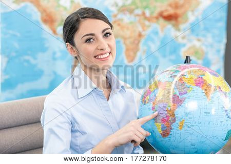 Young woman travel agent choosing destination with globe