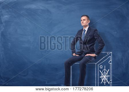 Businessman on blue chalkboard background sitting on a strongbox drawn in white. Business and money. Earning money and keeping them safe.
