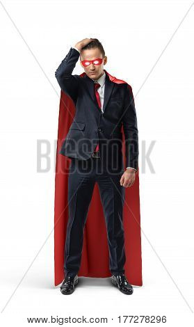 A businessman in a formal suit and superhero cape and mask looking doubtful and holding his head. Business and risk. Success and loss. Credit and expenses.
