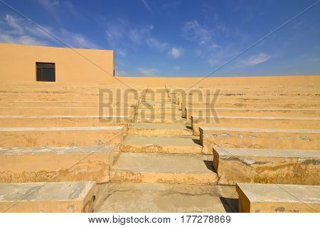 Architectural background with blue sky over pink plastered concrete terrace steps