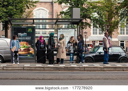 Amsterdam Netherlands - October 3 2016: People of different ethnic groups are waiting in a public transport station. Multicultural diversity issue.