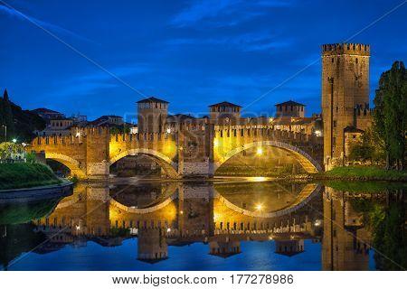 Castelvecchio Bridge reflecting in water at night Verona Italy