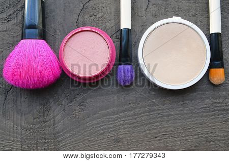 Makeup brushes,compact powder and blush on old wooden background with copy space.Various makeup products.Fashion cosmetic makeup or woman beauty accessories concept.Selective focus.