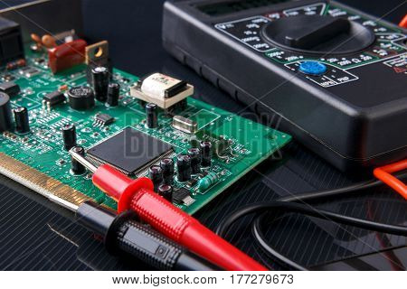 electronic board and digital multimeter on dark background