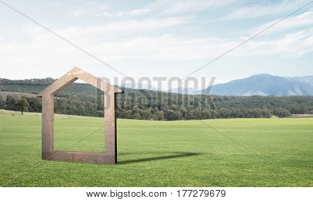 House stone figure as symbol of real estate outdoors against natural landscape