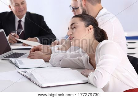 Tired young woman sleeping during conference in office