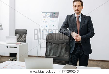 Ready to achieve results. Involved charismatic bearded businessman standing in the office while expressing confidence and looking at the audience