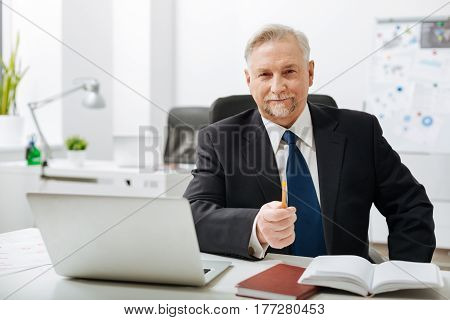 Full of confidence. Cheerful charismatic bearded businessman sitting at the workplace while working and expressing confidence