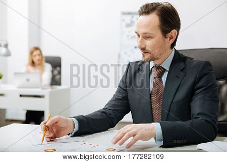 Full of attention. Concentrated positive hardworking businessman sitting in the office while working and becoming familiar with documents
