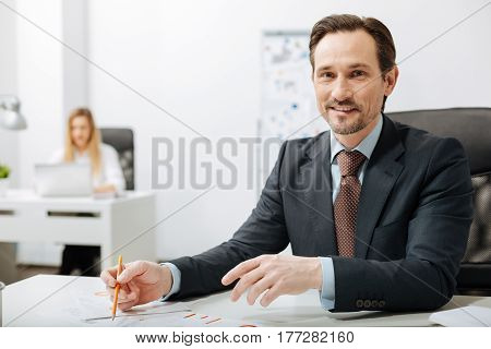 Delighted from my responsibilities. Concentrated positive hardworking businessman sitting in the office while working and becoming familiar with documents