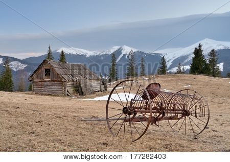 Spring landscape with old agricultural machinery and a wooden barn. A view of the snowy peaks of the mountains. Carpathians, Ukraine, Europe