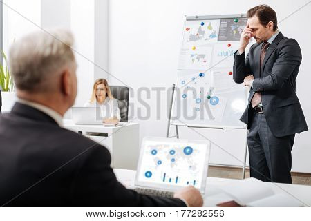 Expressing full incompliance. Upset doubtful dissatisfied employee standing near the whiteboard in the office while working and representing the project to employer
