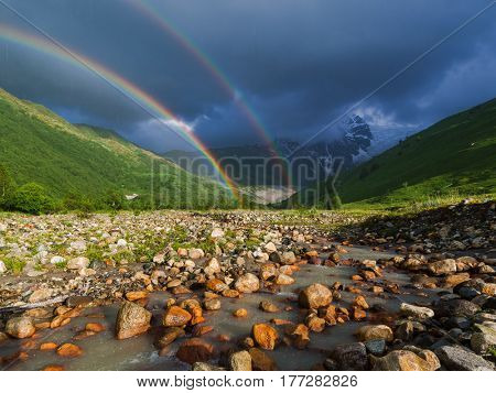 Rainbow in the mountains. Summer landscape with a river, hills and a stormy sky. Rain in the valley.