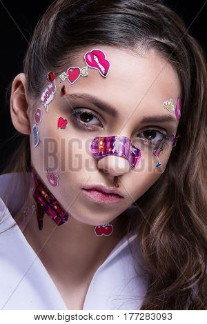 Beautiful Fashion Girl With Luxury Professional Makeup And Funny Emoji Stickers Glued On The Face.